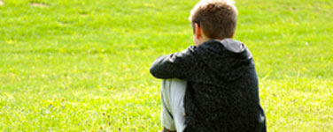 picture of boy sitting in the grass