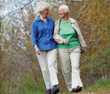 two elderly ladies walking outside, smiling